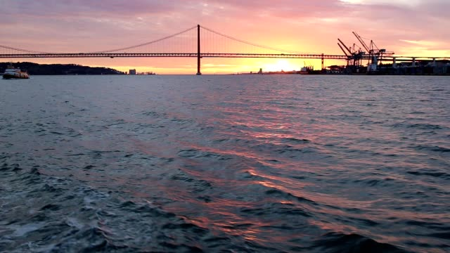 Golden sunset on the background of 25th April Bridge Lisbon video