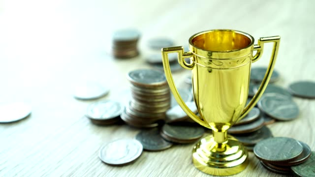 Golden trophy winner with rising money coins for business management profit target in life. Achievement success in currency economic for financial fund.
