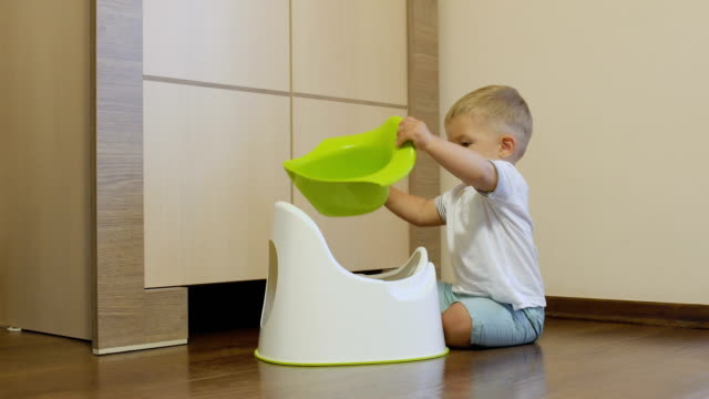 Golden-haired boy plays with his potty video