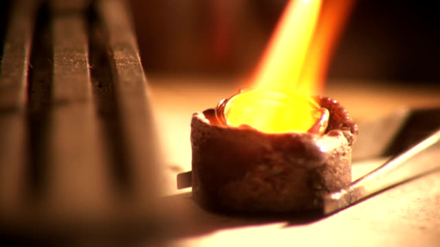 Goldsmith melts gold rings down to liquid in crucible We see an extreme close up of a master goldsmith melting down a pair of rings into liquid inside of a crucible.  He applies the torch to them and slowly they melt away. blacksmith shop stock videos & royalty-free footage