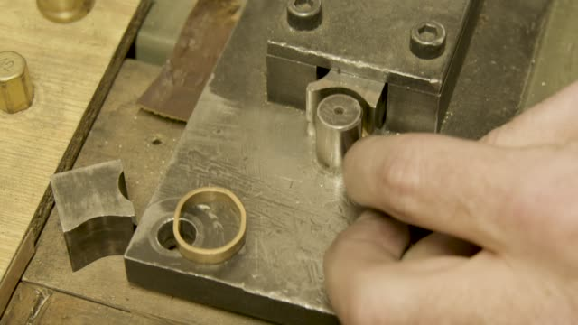 Goldsmith uses a Bending machine to create a gold wedding ring, close up video