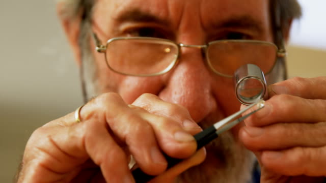 Goldsmith using magnifying glass in workshop 4k Close-up of goldsmith using magnifying glass in workshop 4k magnifying glass stock videos & royalty-free footage