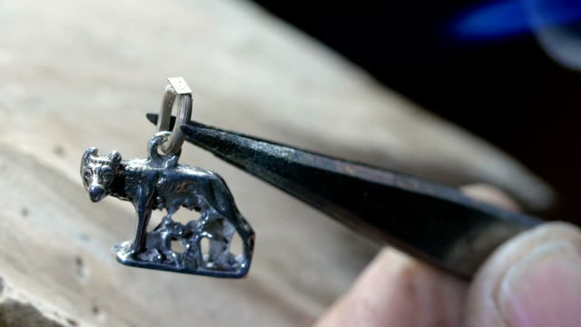 Goldsmith working on a silver pendant with the symbol of Rome video