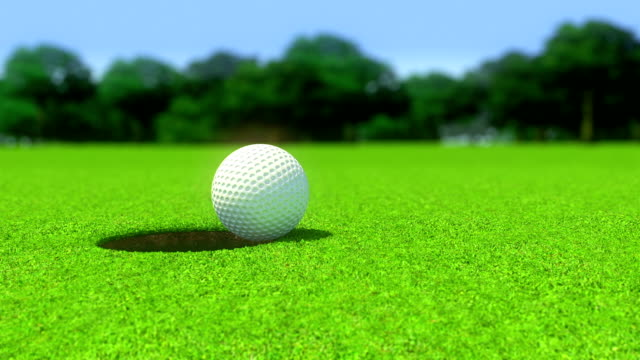 Golf ball into a hole closeup video