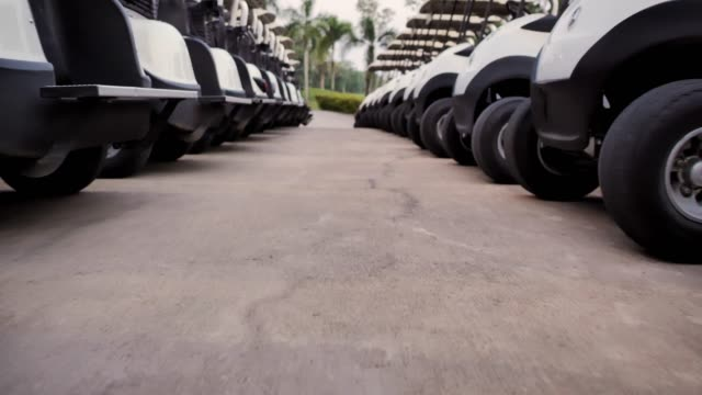 Golf cars or golf carts in a row outdoors on a sunny spring day.Sports Cinemagraphs - vídeo