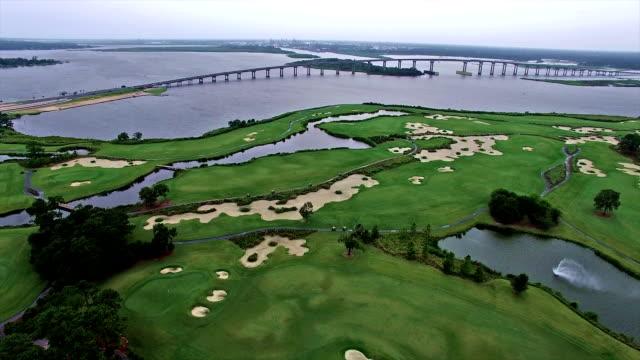 vídeos de stock, filmes e b-roll de campo de golfe em louisiana com ponte ao fundo em lake charles - baía