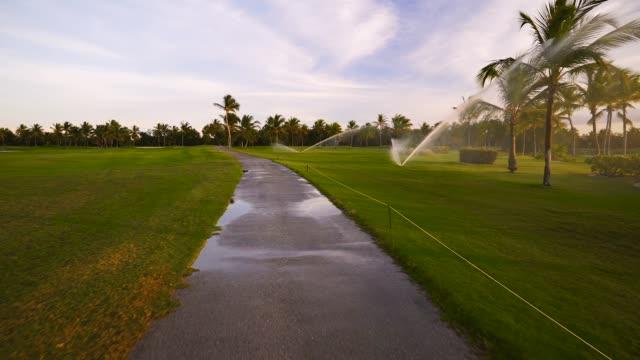 Golf course sprinkler on fairway during golden sunset