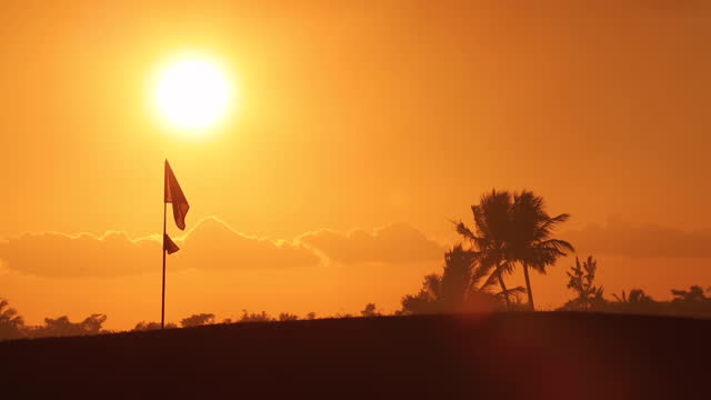 Golf course with flagstick, lake and palm trees silhouettes on sunset. Golfing on tropical island