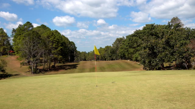 Golf flag on windy in golf course and beautiful fairway and layout on blue sky and green grass