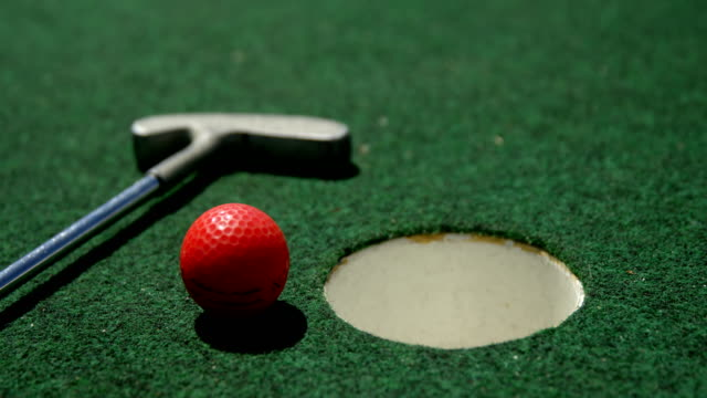 Golf putter and golf ball on a artificial turf 4k video