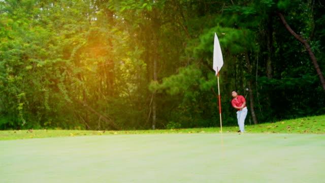 ゴルフ スポーツ コンセプト、美しいフェアウェイとレイアウトのゴルフ場のバンカーにゴルフボールを打つゴルファー。緑と風の赤い旗。 - ゴルフ点の映像素材/bロール