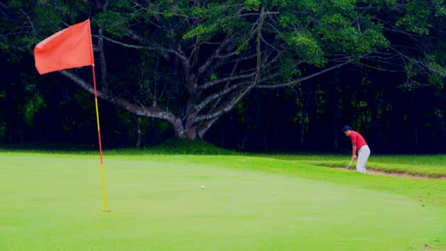 golf spor kavramı, bunker güzel fairway ve düzen içinde golf sahasının üzerinde golf topu vurmak golfçü. kırmızı bayrak yeşil ve bir rüzgar esiyor. - mountain top stok videoları ve detay görüntü çekimi