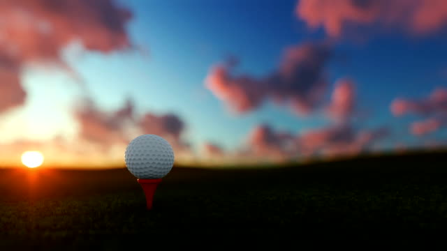 Golfball on tee against beautiful timelapse sunset video