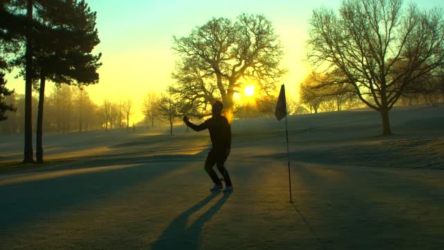 Ein Golfer feiert bei Sonnenaufgang einen Superputt. – Video