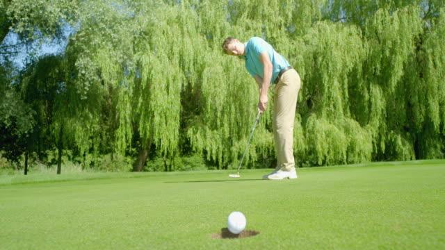 Ein Golfer hat eine Linie auf seinem Golfball gezogen, um zu helfen, sich mit dem Becher zu reihen und den Putt hier zu versenken, er trifft einen tollen Putt und bohrt ihn o – Video