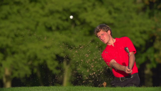 A Golfer hits a great shot out of a sand trap and celebrates holing the shot. video