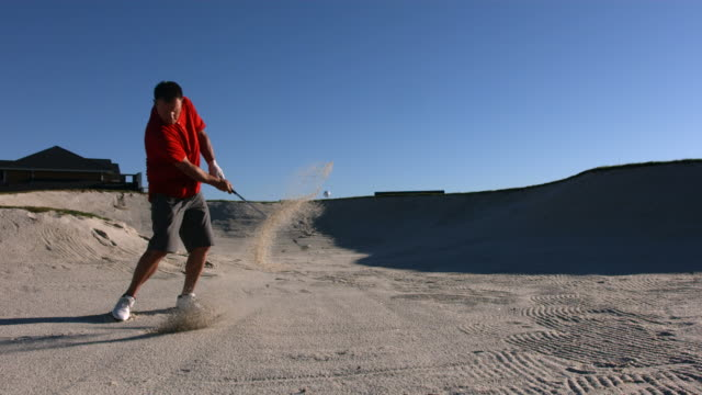 Golfer hits ball from sand trap, slow motion video