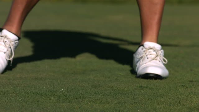 Golfer hits ball off tee, slow motion video