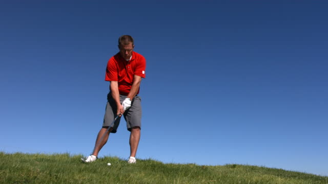 Golfer hits ball, slow motion video
