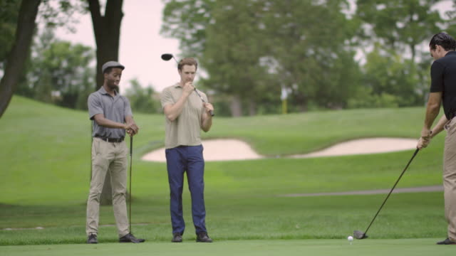 Golfer Hitting A Tee Shot With Group Watching video