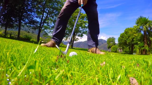 golfer hitting den golfball auf dem nassen raugras an einem sonnigen tag - rau stock-videos und b-roll-filmmaterial