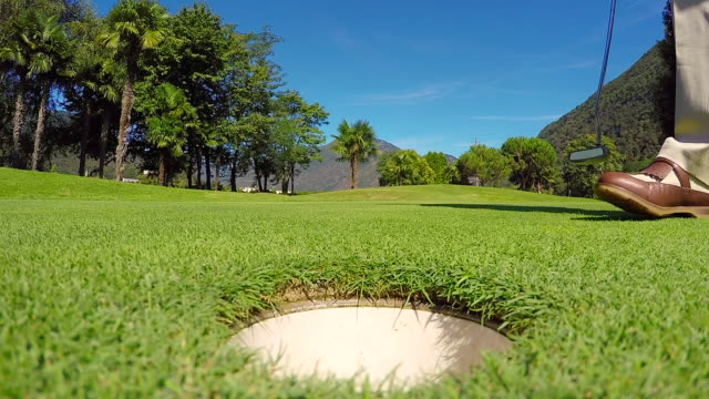golfçü yeşil koyarak golf hole itibaren golf ball pick up - mountain top stok videoları ve detay görüntü çekimi