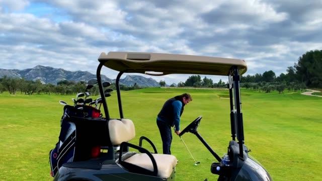 golfçü onun golf arabası ile golf sahası'nda playing - mountain top stok videoları ve detay görüntü çekimi