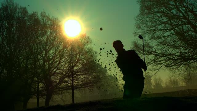 Ein Golfer spielt bei Sonnenaufgang einen tollen Schuss aus einer Sandfalle. – Video