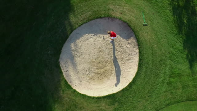 A Golfer plays a shot out of a sand trap and celebrates. video