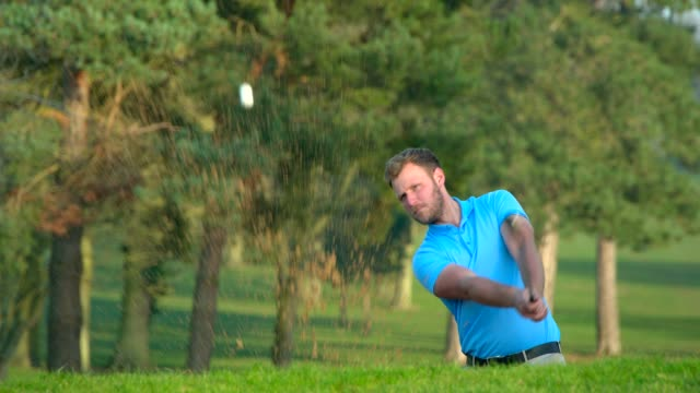 Ein Golfer spielt in Zeitlupe einen Schuss aus einer Sandfalle. – Video