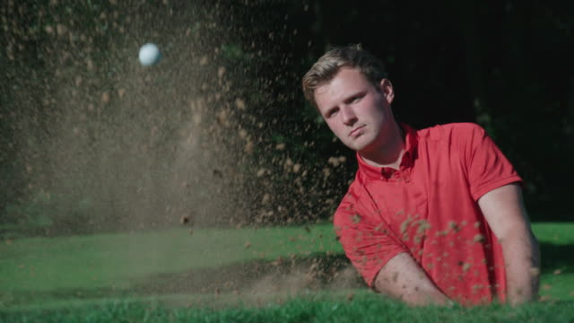 A Golfer plays an explosive shot in slow motion from a sand trap. video