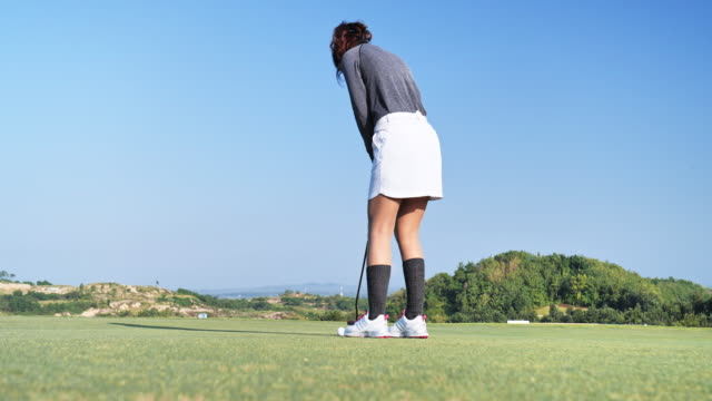 Golfer putt ball to hole on green golf course, sky scene background.