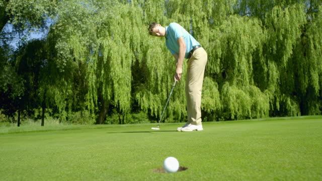 Ein Golfer putts und ist verlockend nah an holing den Golfball. – Video