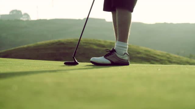 Golfer sinks a putt at sunset shot in HD video
