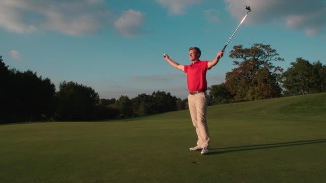 Ein Golfer sinkt einen Putt, küsst den Golfball und feiert. – Video