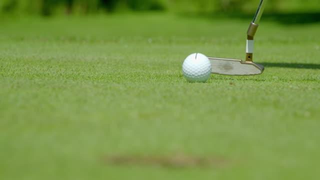 un golfista affonda un putt!  il golfista ha tracciato una linea sulla pallina da golf per mirare in modo più accurato, ha funzionato! - rack focus video stock e b–roll