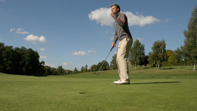 Ein Golfer sinkt das Putten und feiert. – Video