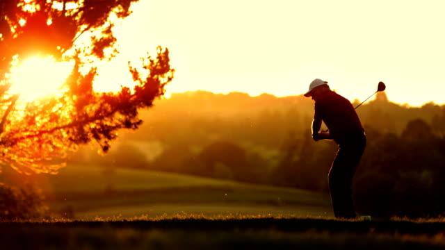 Una persona WS golfista golpear desde el tee en la puesta de sol - vídeo