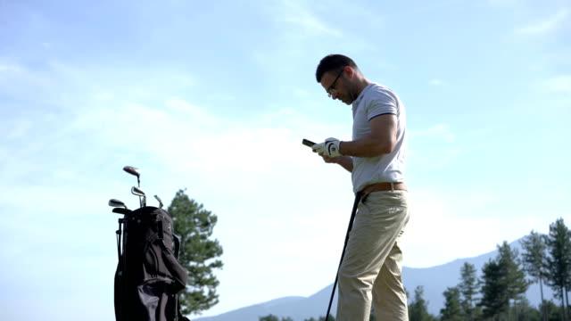 vidéos et rushes de envoyer des sms sur le téléphone tout en jouant golfeur - golf