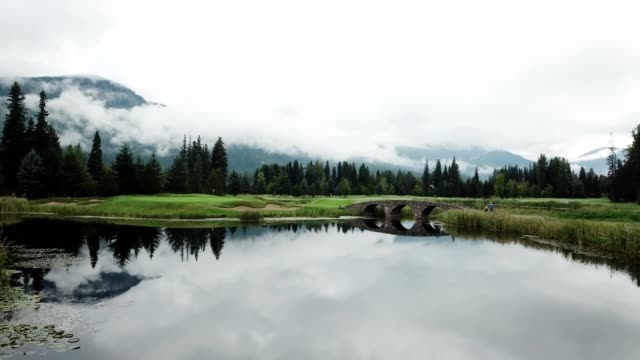 Golfers cross the lake towards the putting green