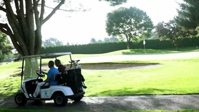 Golfers ride in golf cart.