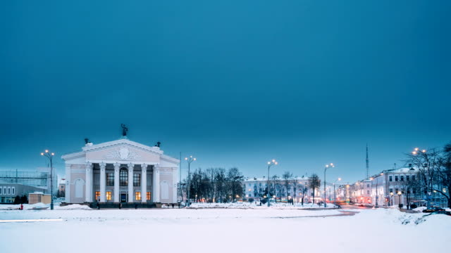 gomel, belarus. time lapse time-lapse from day to night. traffic and light trails near building of gomel regional drama theatre on the lenin square in winter season. change of day to night - estonia filmów i materiałów b-roll