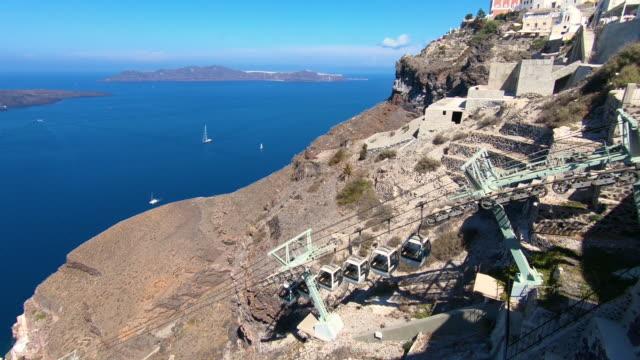 gondola going up mountain in fira, thira overlooking the caldera volcanic aegean sea with greek orthodox cross in santorini greece - isole egee video stock e b–roll