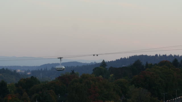 Gondola lift trams move over trees and the traffic below in Portland, Oregon Gondola lift trams move over trees and the traffic below in Portland, Oregon cable car stock videos & royalty-free footage