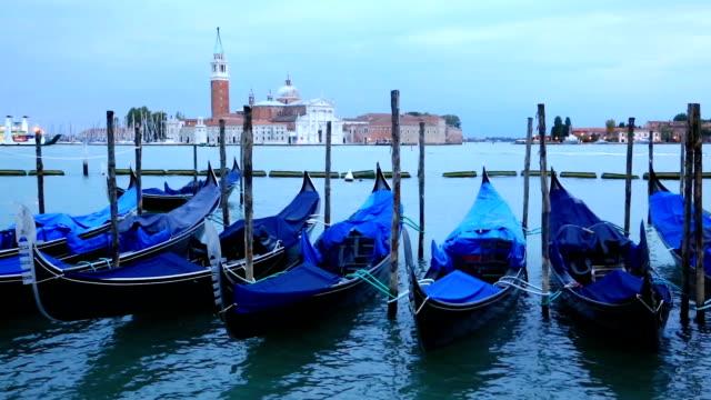 Gondolas moored by Saint Mark square with San Giorgio di Maggiore church video
