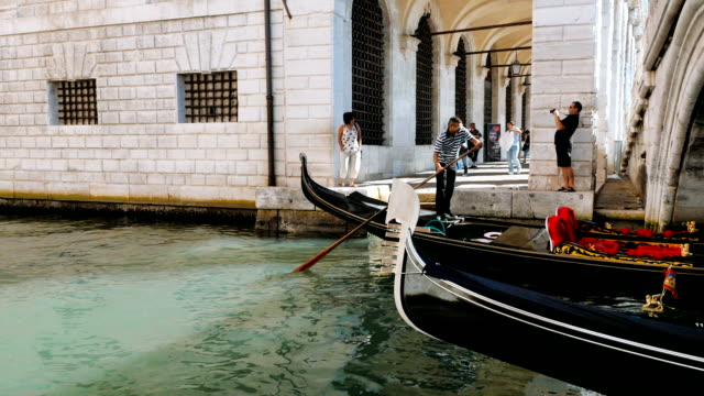 gondolas sailing in a Venetian canal passing under a bridge video