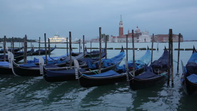 vídeos de stock e filmes b-roll de gondolas agitar na água no grande canal, veneza - lago maggiore