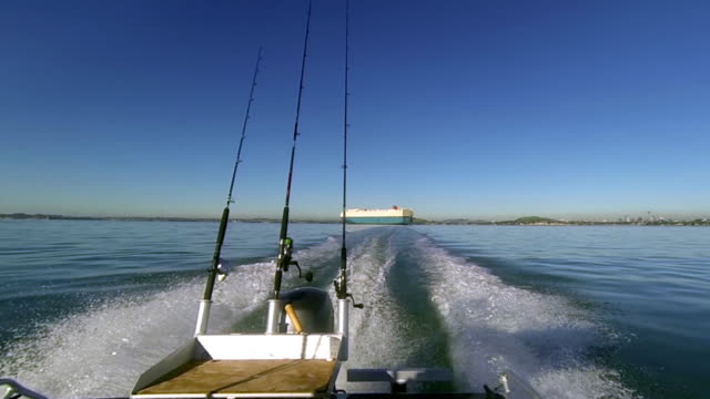 Gone fishing! Motor boat view looking back towards cargo ship. video