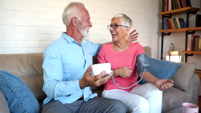 Good and healthy news for a senior couple measuring blood pressure Lovely and cheerful looking senior couple measuring blood pressure to one another at home. blood pressure gauge stock videos & royalty-free footage