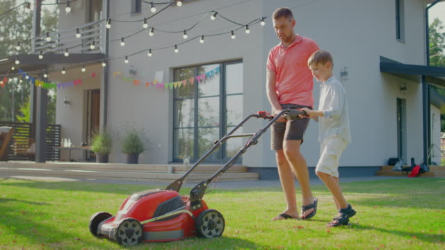 Good Father Teaches Son How to Use Walk Behind Lawn Mower, They Push it Together, Cutting Grass. Family Spending Time Together on a Sunny Day. Good Father Teaches Son How to Use Walk Behind Lawn Mower, They Push it Together, Cutting Grass. Family Spending Time Together on a Sunny Day. Shot on RED EPIC-W 8K Helium Cinema Camera. chores stock videos & royalty-free footage